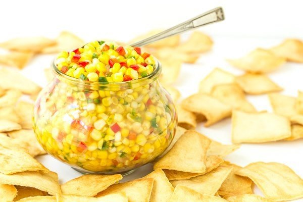 Photo of a jar of Trader Joe's Corn and Chile Salsa surrounded by pita chips. A spoon is placed in the salsa.