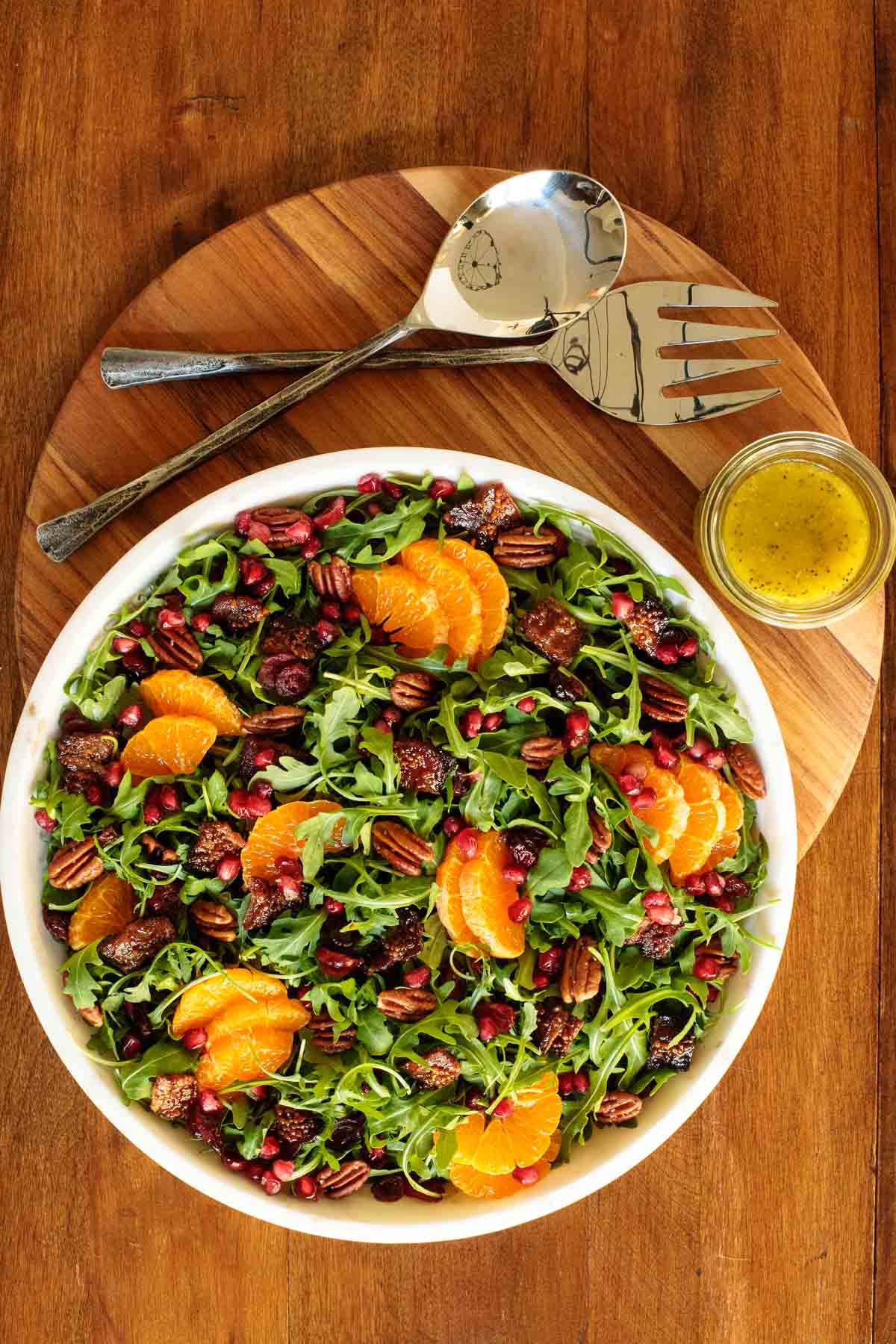 Overhead photo of a white stone salad bowl of Cranberry Clementine Arugula Salad on a wood presentation platter.