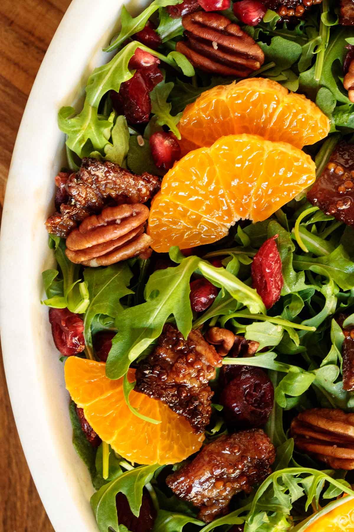 Extreme closeup photo of a bowl of Cranberry Clementine Arugula Salad.