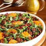 Vertical picture of cranberry clementine salad in a white bowl with a small cruet of dressing in the background
