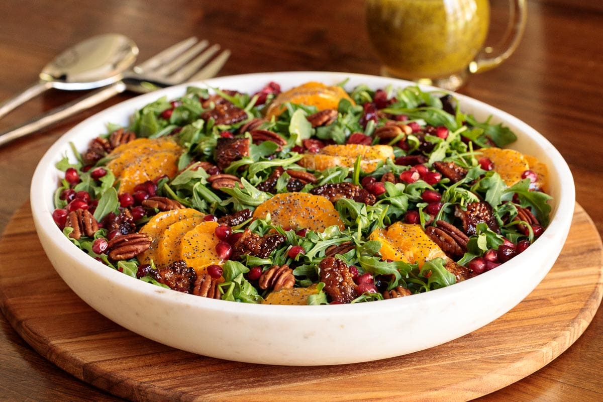 Photo of a white stone bowl of Cranberry Clementine Arugula Salad on a wood presentation board.