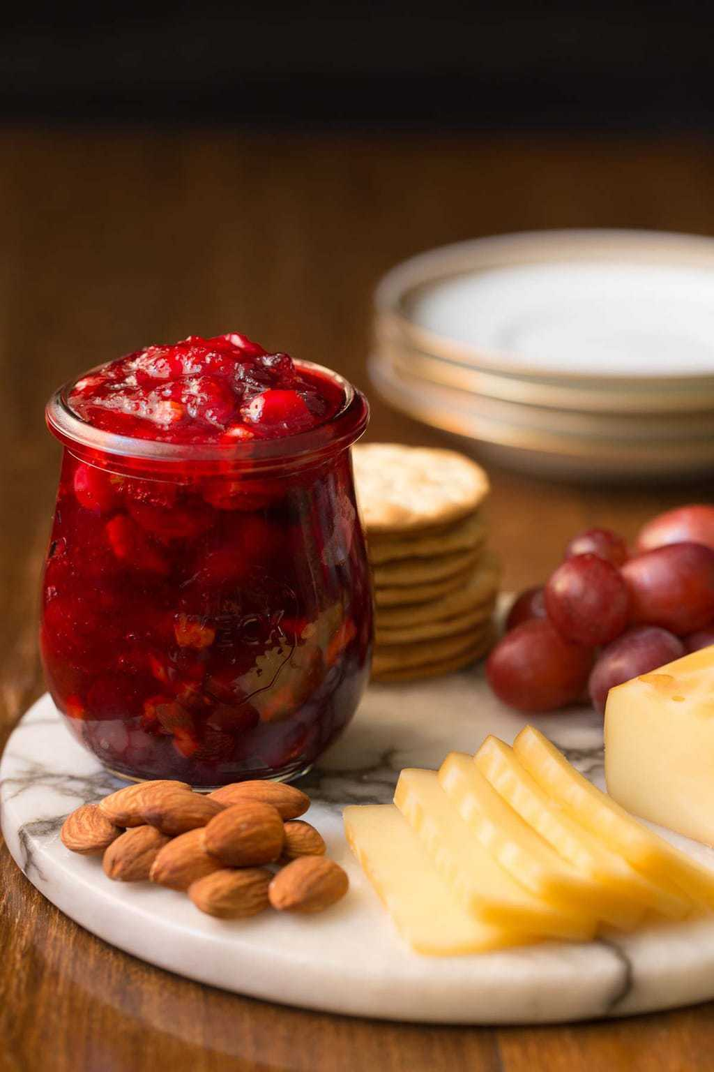 Photo of a marble appetizer tray with Cranberry Clementine Conserves, cheese, almonds, crackers and red grapes.