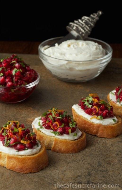 Vertical photo of Cranberry Pomegranate Bruschetta lined up on a slate platter.