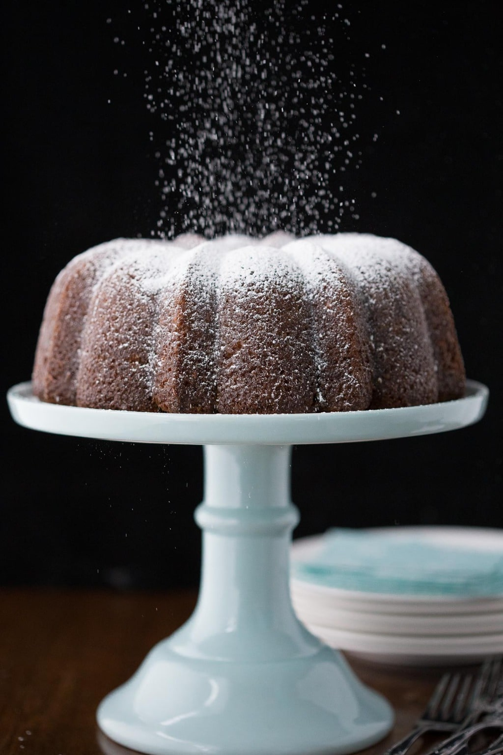 Vertical photo of a Crazy Delicious Carrot Cake on a light blue cake stand with powdered sugar falling down on the top.