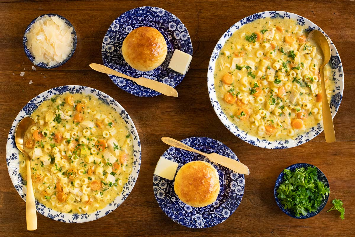 Overhead vertical photo of two serving bowls of Creamy Chicken Parmesan Pasta Soup on a wood table with fresh baked Brioche Buns.