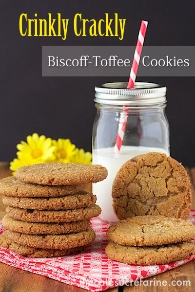 Photo of two stacks of Biscoff Toffee Cookies on a red and white napkin with a Ball jar of milk and a straw in the background.