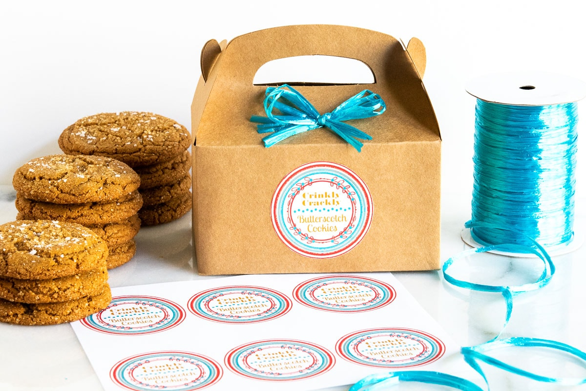 Horizontal photo of Crinkly Crackly Butterscotch Cookies surrounding a gift box with custom labels for gift giving.