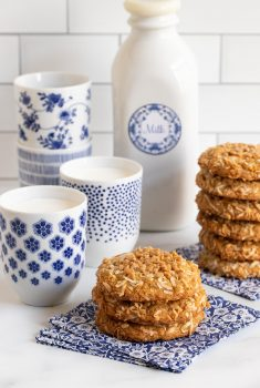 Vertical photo of stacks of Crispy Chewy Carolina Coconut Cookies on blue and white patterned napkins with cups and a bottle of milk in the background.