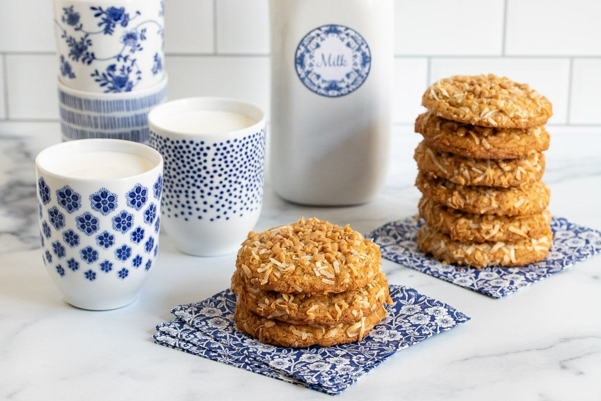 Horizontal photo of stacks of Carolina Coconut Cookies on blue and white patterned napkins with glasses and a bottle of milk in the background.