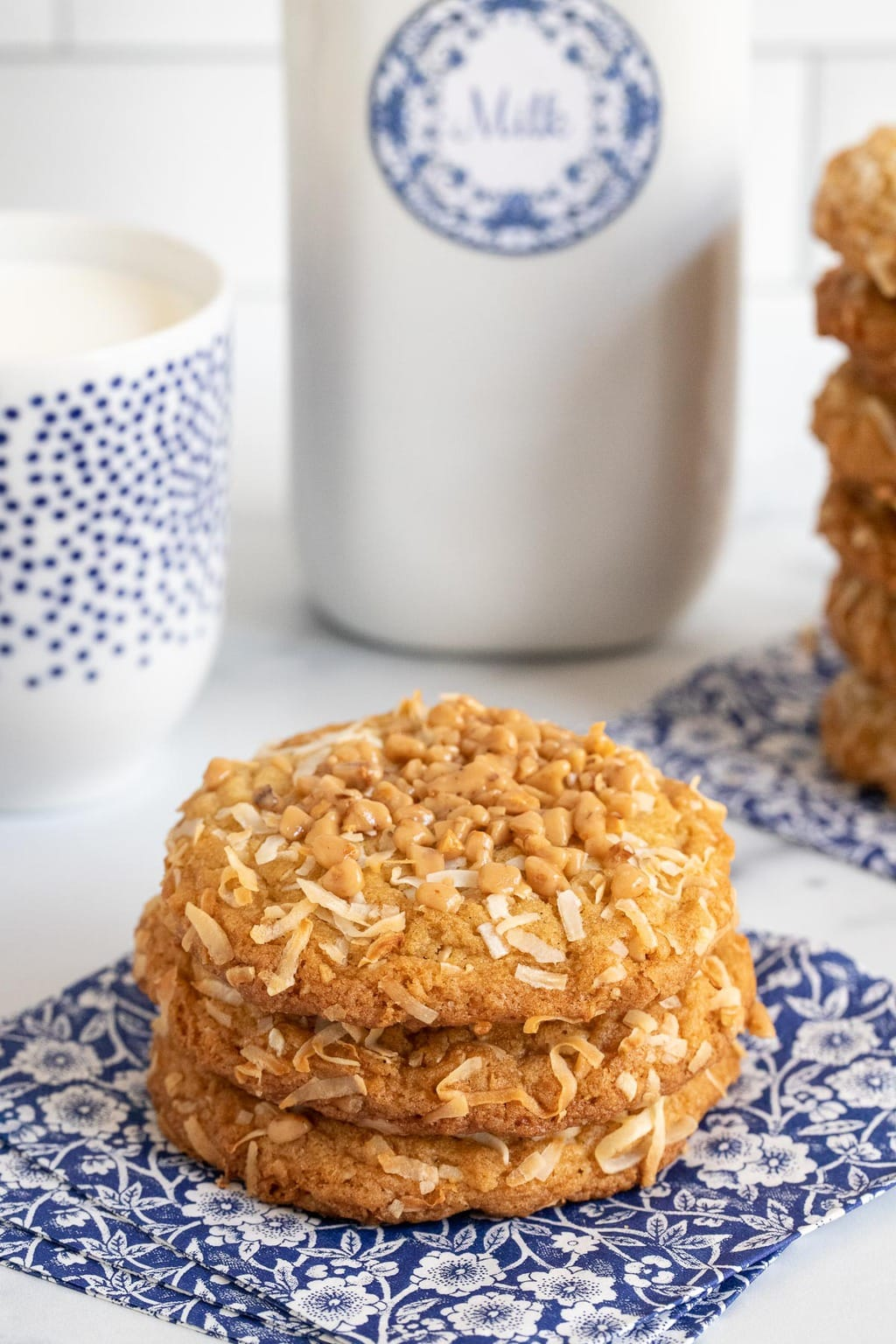 Vertical photo of a small stack of Crispy Chewy Carolina Coconut Cookies on blue and white patterned napkins with glasses and a bottle of milk in the background.