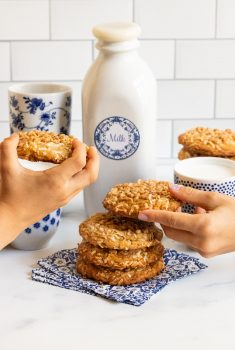 Vertical photo of a stack of Crispy Chewy Carolina Coconut Cookies with two hands taking two of the cookies.