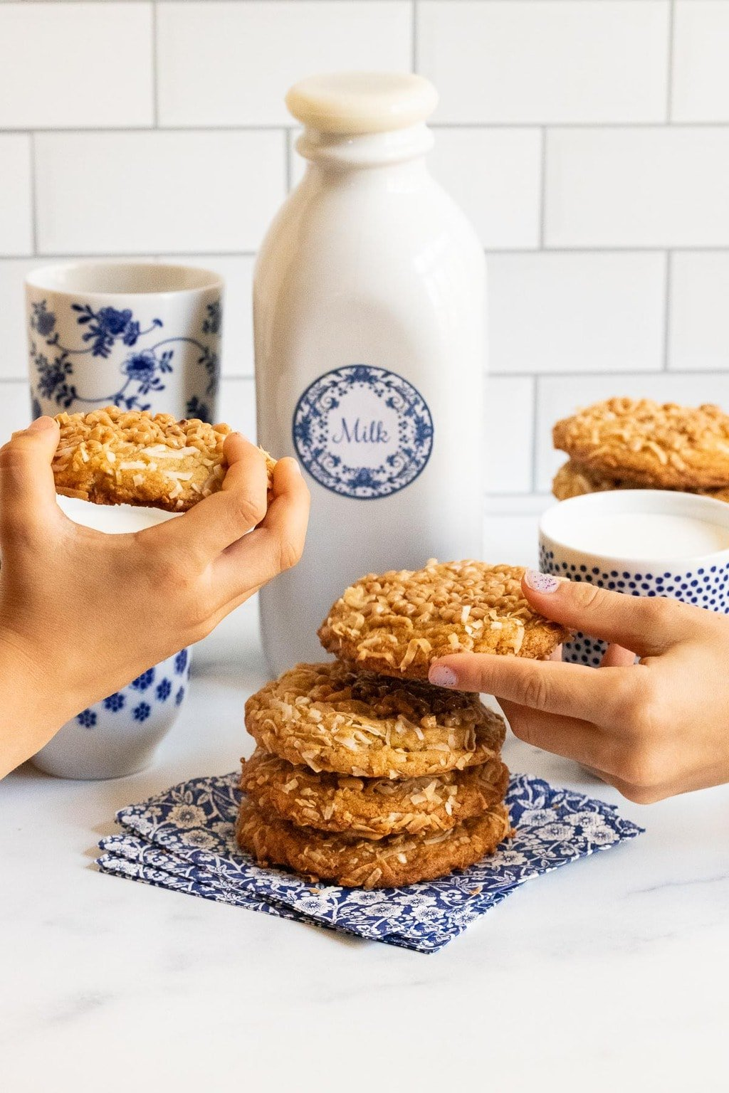 Vertical photo of a batch of Crispy Chewy Carolina Coconut Cookies with two kids hands helping themselves to the cookies.