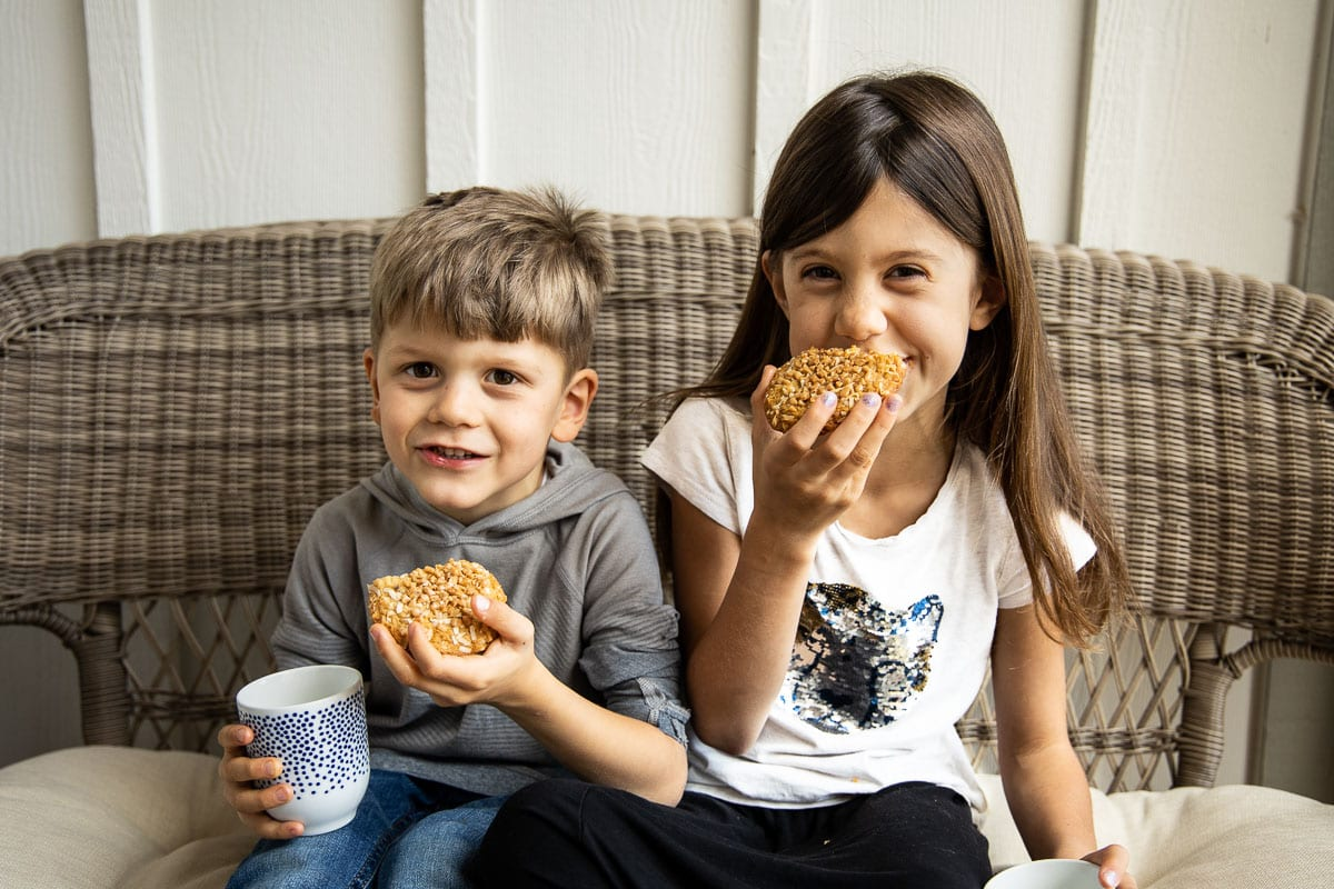 Horizontal photo of two children enjoying Crispy Chewy Carolina Coconut Cookies on a porch couch with cups of milk.