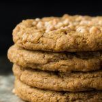 Vertical picture of Crispy Chewy Toffee Pumpkin Cookies in a stack on a black background