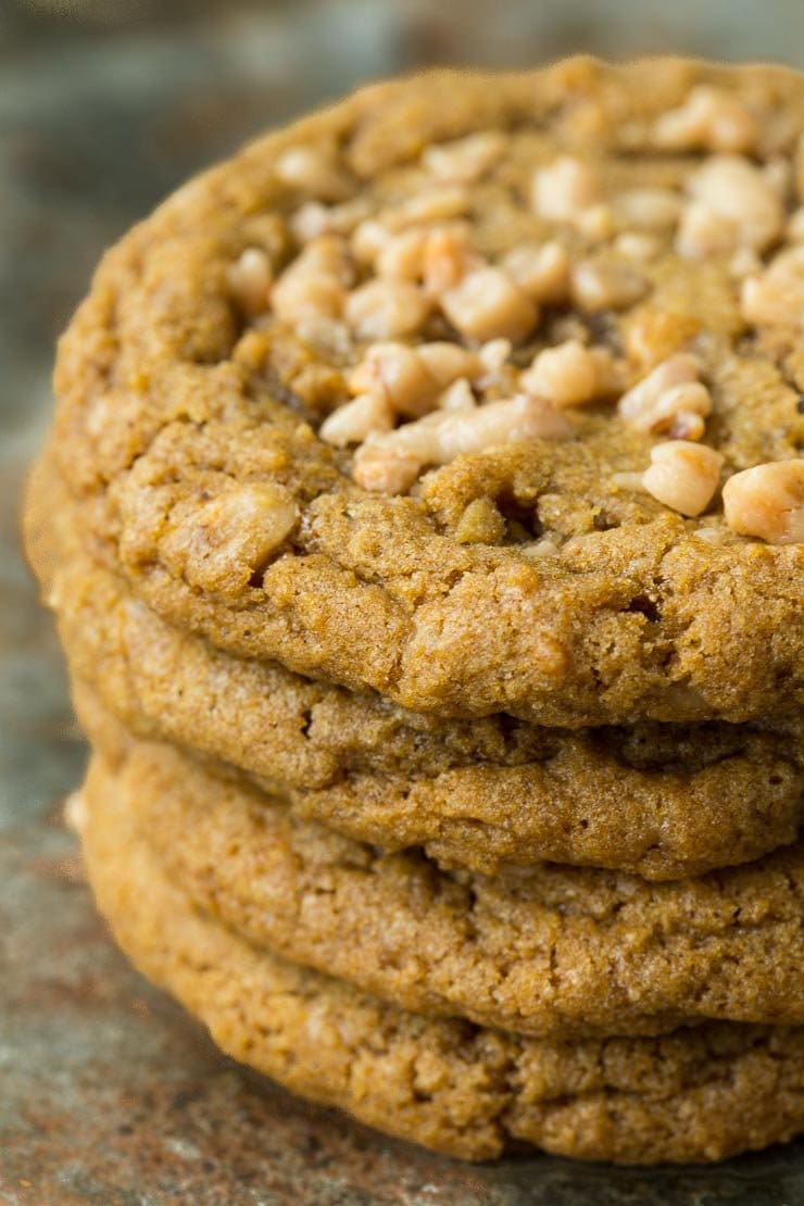 Ultra closeup of a stack of Crispy Chewy Toffee Pumpkin Cookies on a slate table.