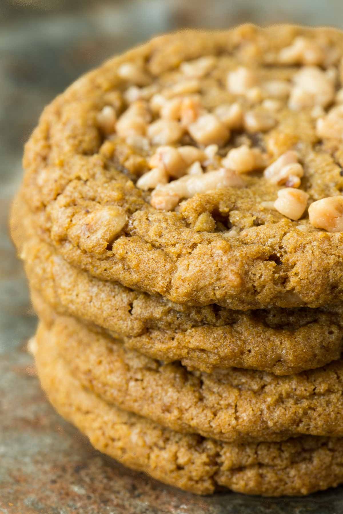 Closeup photo of a stack of Crispy, Chewy Toffee Pumpkin Cookies on a slate surface.