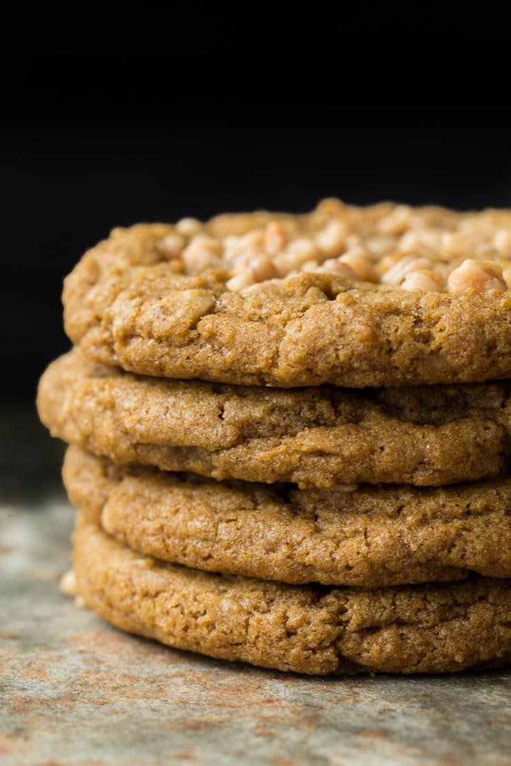 Photo of a stack of Crispy, Chewy Toffee Pumpkin Cookies on a slate table and a black background.
