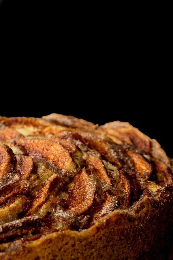 A side closeup photo of the top of a Danish Apple Cake against a black background.