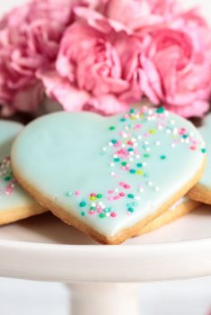 Vertical close up picture of Valentine heart cookies with icing and sprinkles