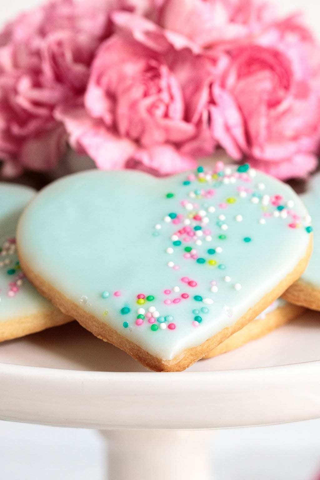 Vertical closeup photo of Dip, Drip and Flip Shortbread Valentine Heart Cookies decorated with icing and sprinkles .