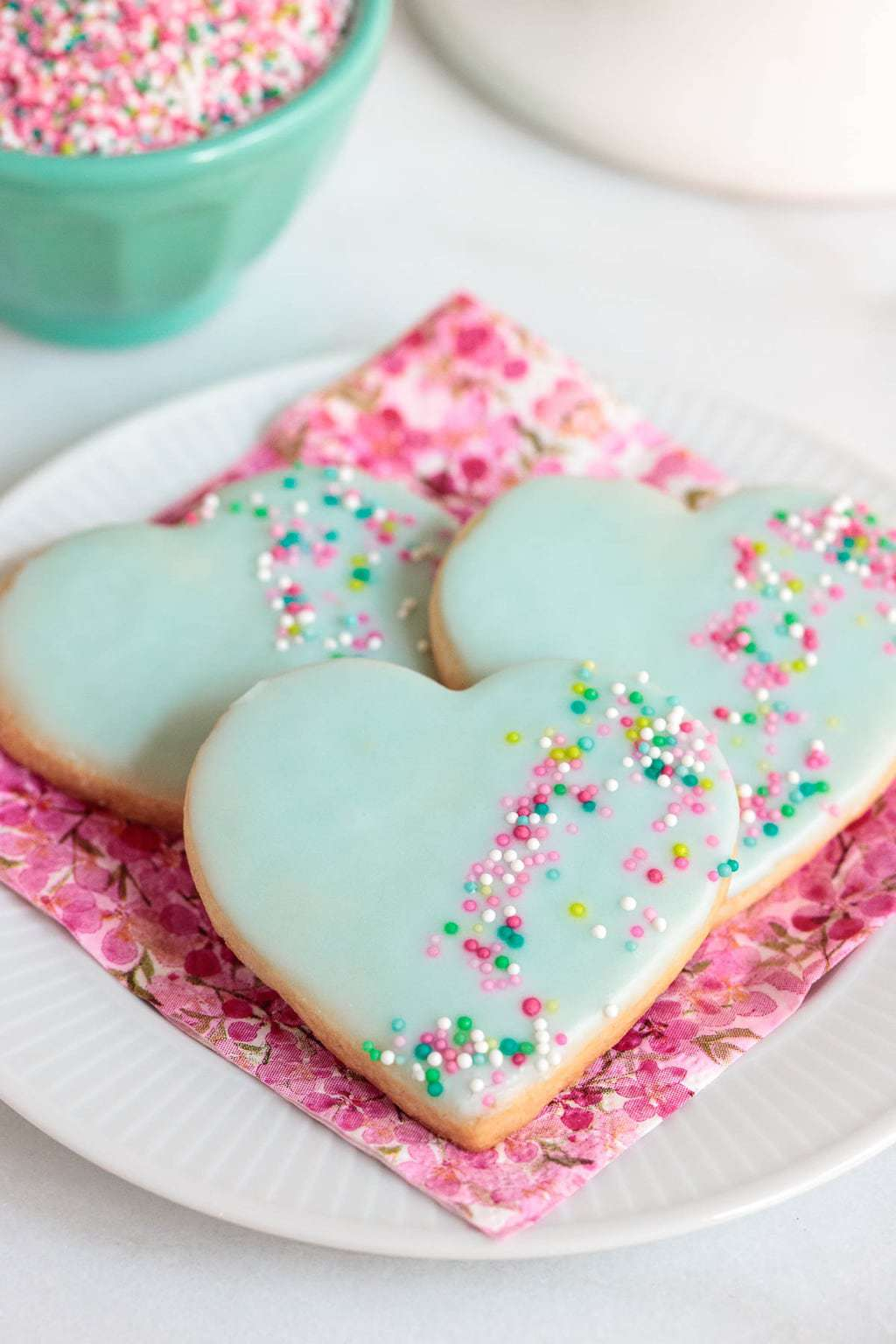 Vertical closeup photo of Valentine Shortbread Heart Cookies on a pink patterned napkin