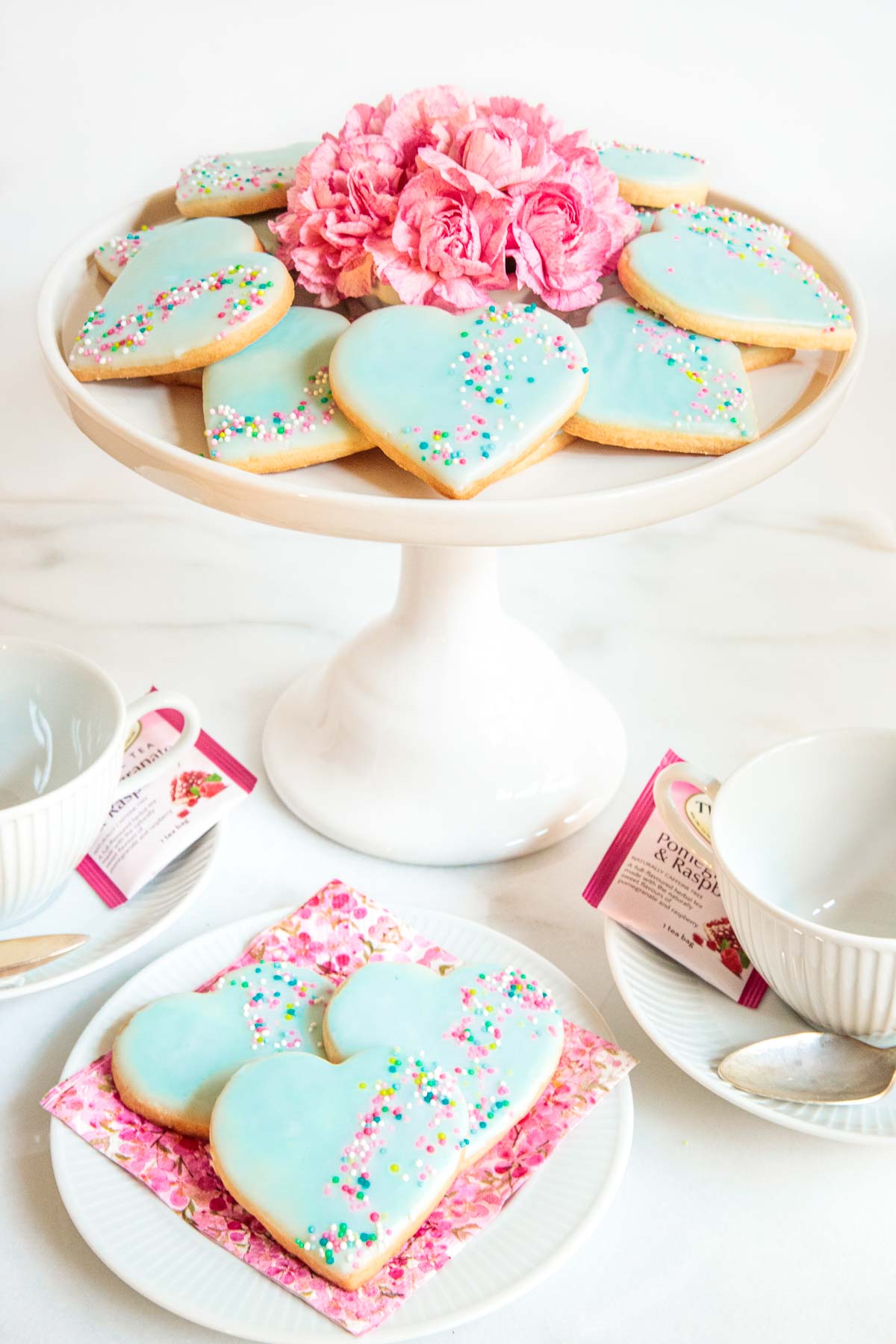 Photo of a white porcelain pedestal plate filled with Dip, Drip and Flip Shortbread Valentine Cookies.