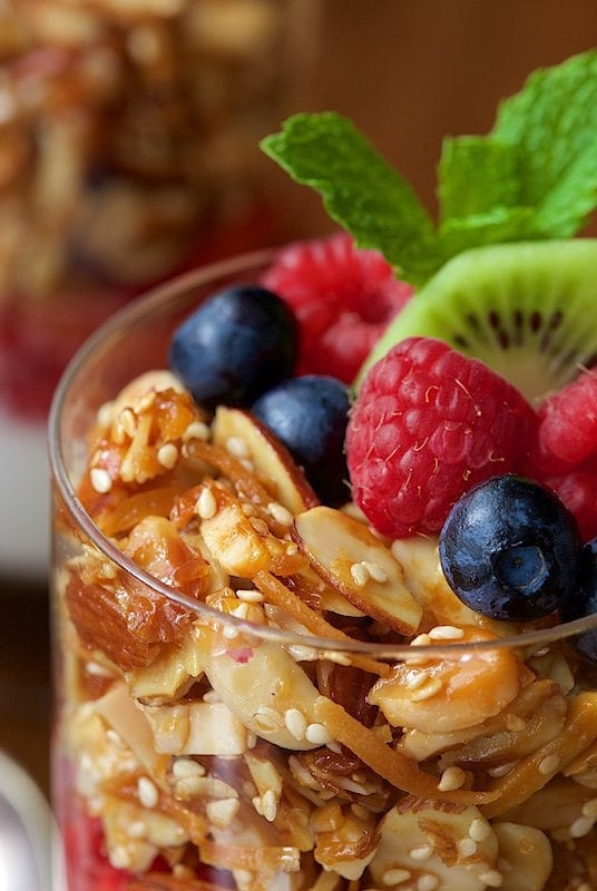 Vertical closeup image of Double Almond Paleo Granola with fresh fruit.