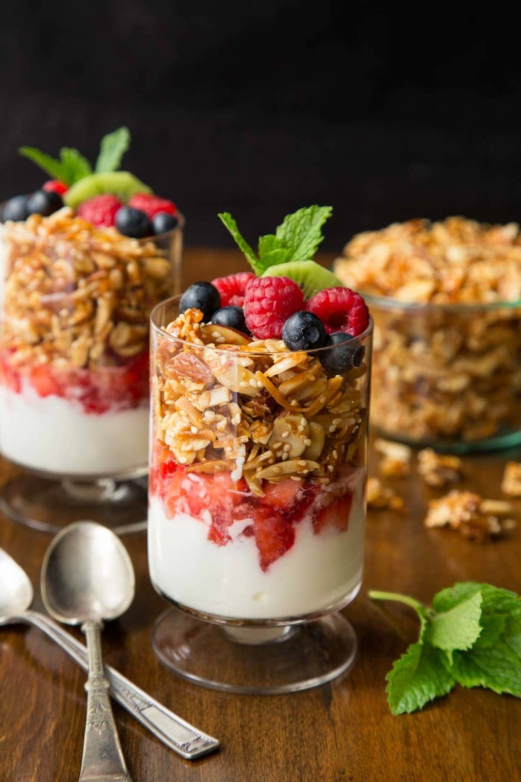 Vertical photo of Double Almond Paleo Granola parfaits with fresh fruit on a wood table.