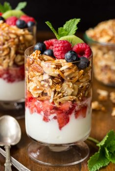 Vertical closeup photo of Double Almond Paleo Granola in parfait glasses with fruit and yogurt.