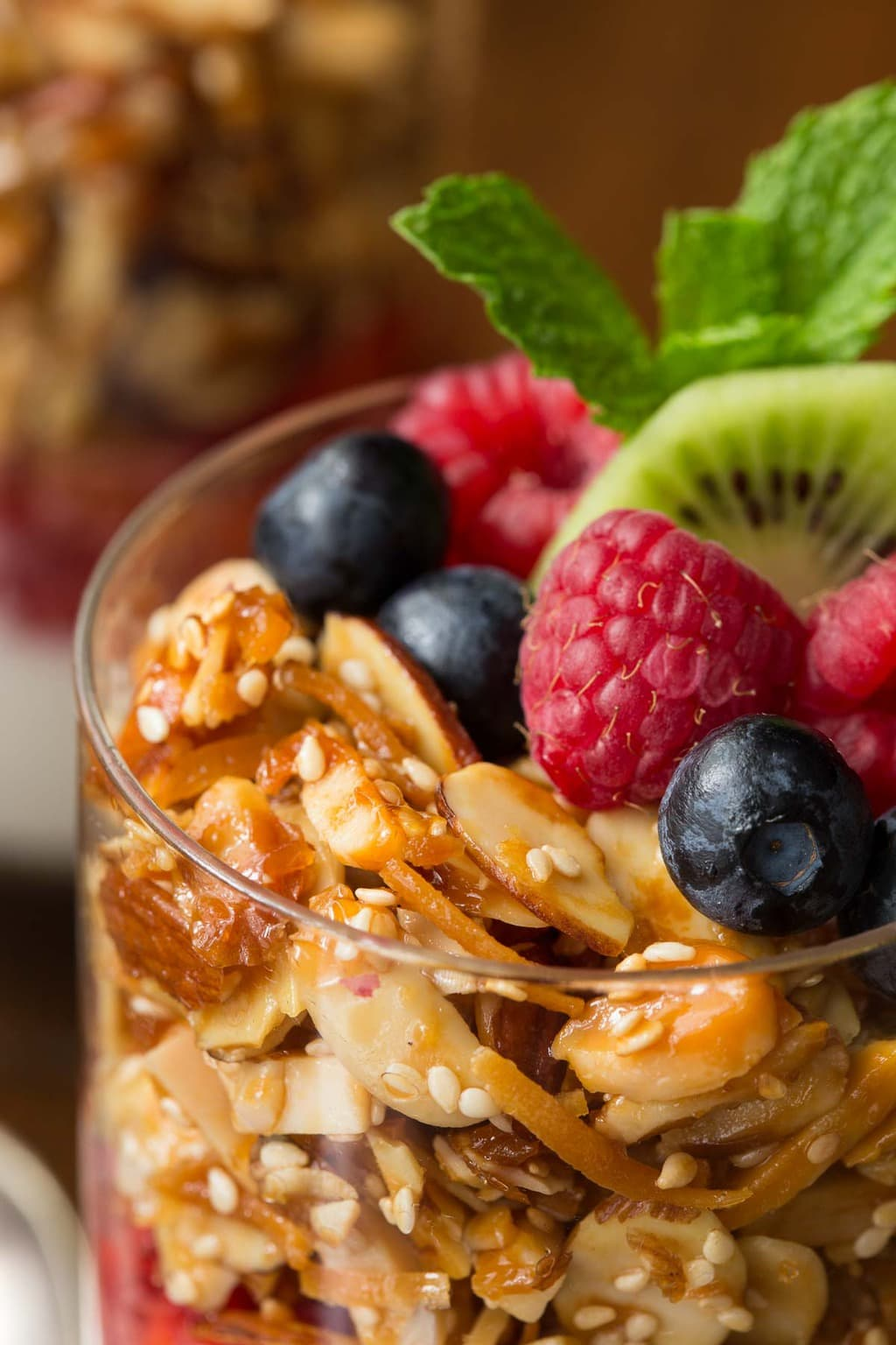 Vertical closeup photo of Double Almond Paleo Granola in a serving glass garnished with fresh fruit.