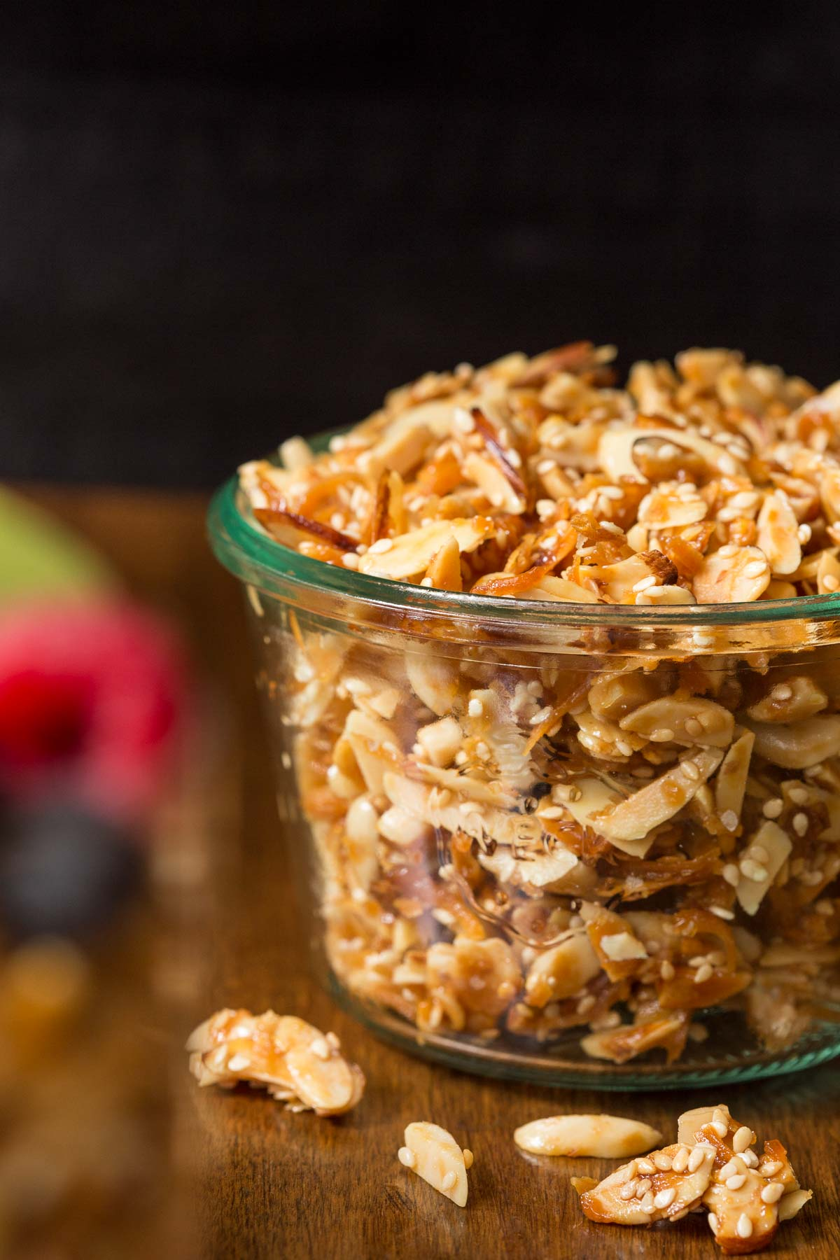 Vertical closeup photo of a Weck jar full of Double Almond Paleo Granola on a wood table with fruit in the background and pieces of the granola in the foreground.