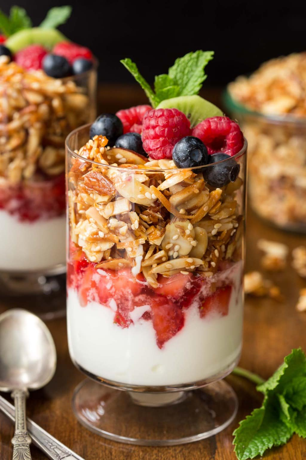 Vertical photo of Double Almond Paleo Granola in parfait glasses with fresh fruit and yogurt.