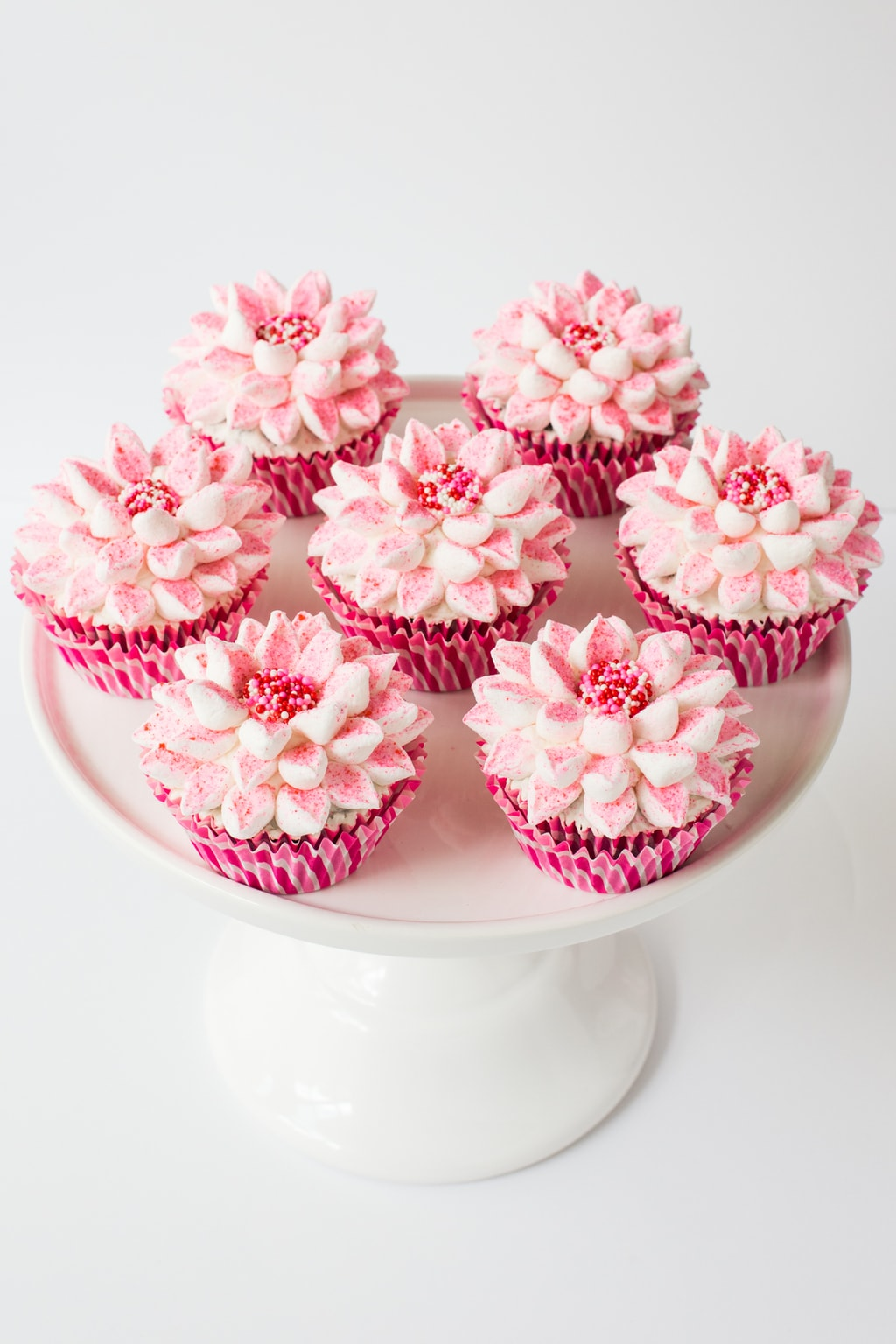 Vertical picture of poinsettia cupcakes on a white cake stand