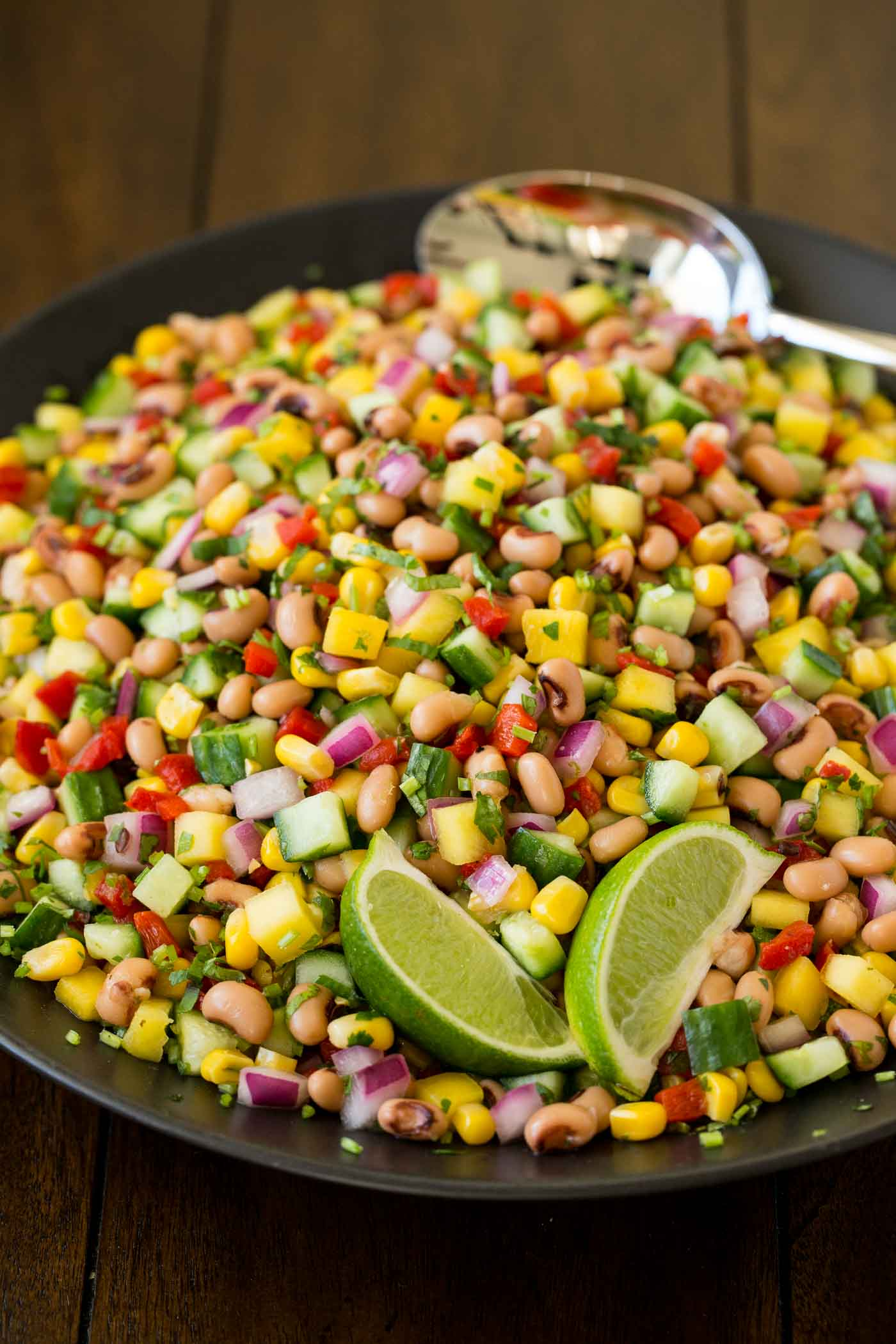 Photo of a black serving dish of Black-Eyed Pea Salad garnished with wedges of lime on a wood table.