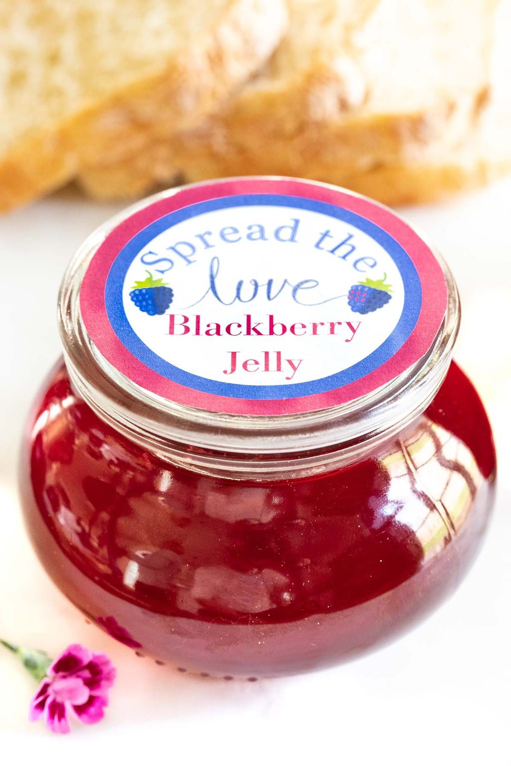 Vertical closeup photo of a glass Weck jar of Easy Blackberry Jelly with a custom gift label on top.