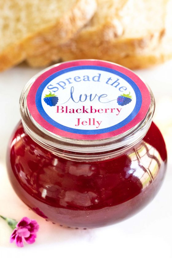 """Vertical photo of a glass jar of Easy Blackberry Jelly with a home made label on top saying, """"Spread the love Blackberry Jelly"""" A loaf of fresh homemade bread is in the background."""