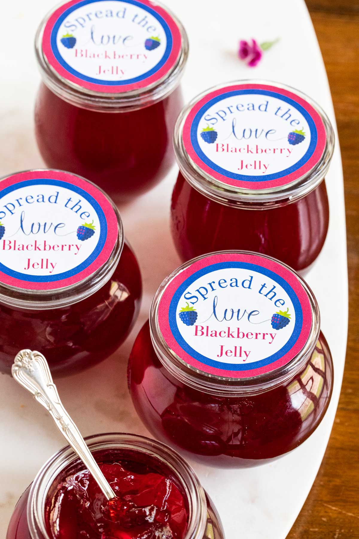 Vertical photo of a group of glass jars of Easy Blackberry Jelly with printed colored labels on the lids.