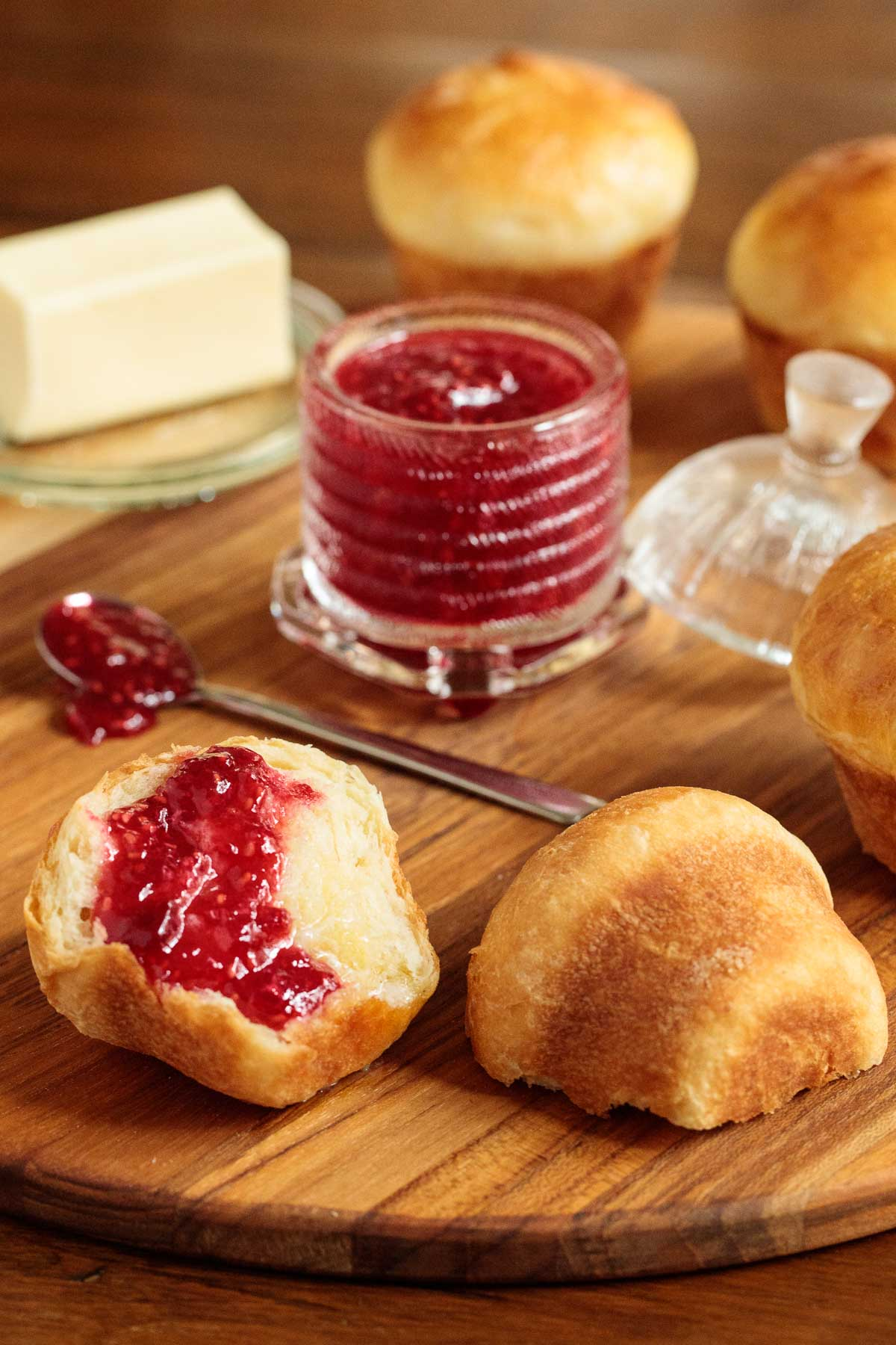 Vertical photo of Easy Brioche Dinner Rolls on a wood platter with raspberry jam on the rolls.