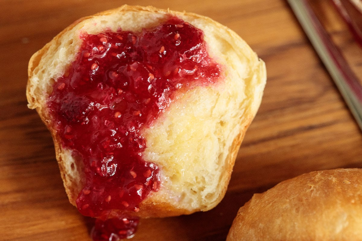 Extreme closeup of a Ridiculously Easy Brioche Dinner Roll spread with butter and raspberry jam.