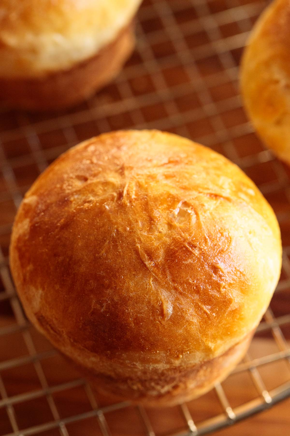 Overhead closeup photo of an Ridiculously Easy Brioche Dinner Roll on a cooling rack.
