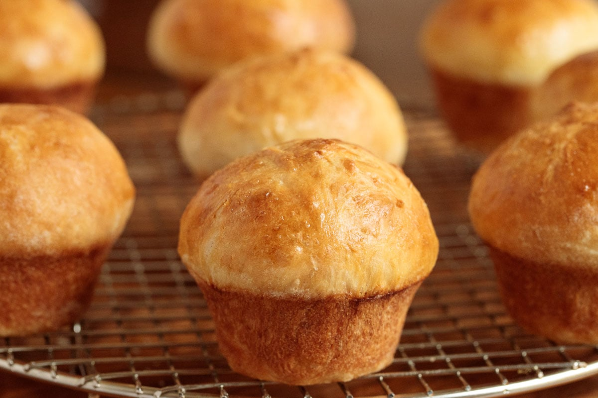 Photo of a batch of Ridiculously Easy Brioche Dinner Rolls on a silver cooling rack.