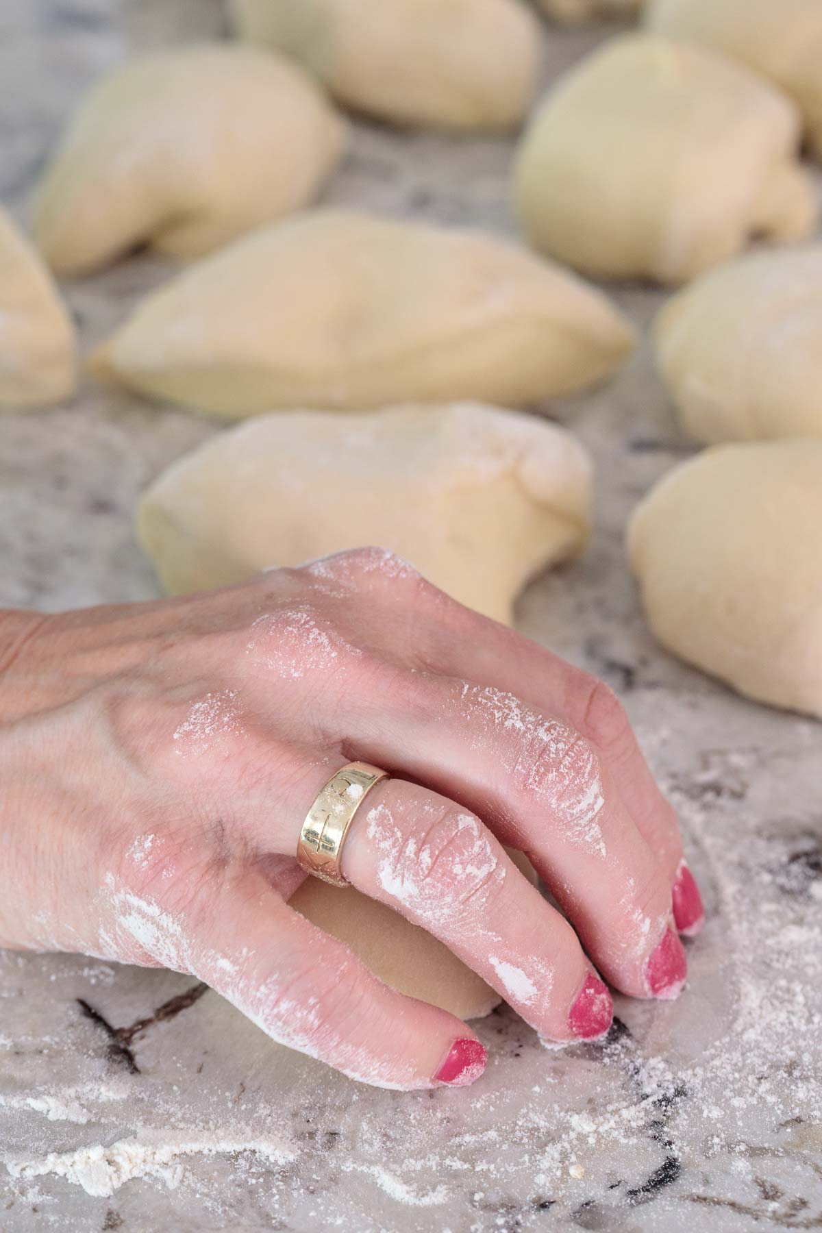 Photo of a hand rolling an Easy Buttermilk Brioche Bun.