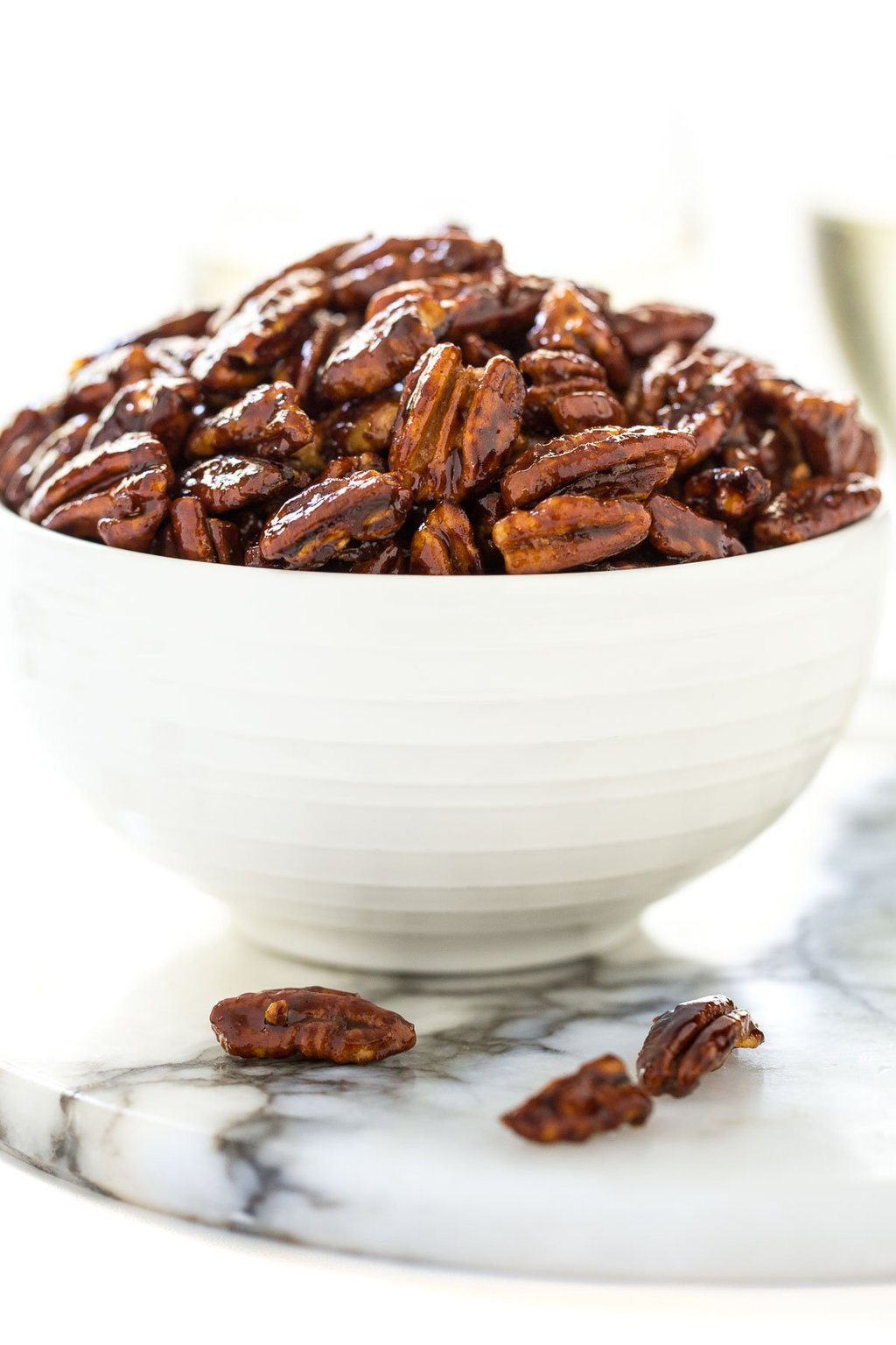 Vertical closeup photo of Easy Candied Pecans in a white bowl.