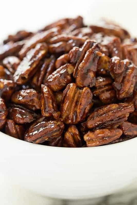 Closeup photo of a white bowl filled with Easy Candied Pecans.