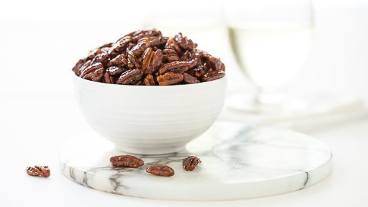 Photo of a white bowl of Easy Candied Pecans on a round white and grey marble slab.