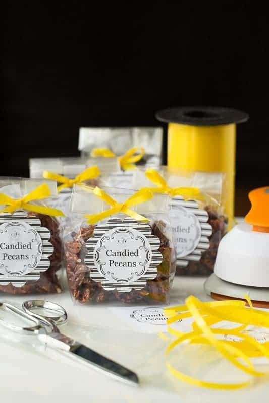 Photo of gift bags of Easy Candied Pecans tied with yellow ribbon and surrounded by gift-making supplies.