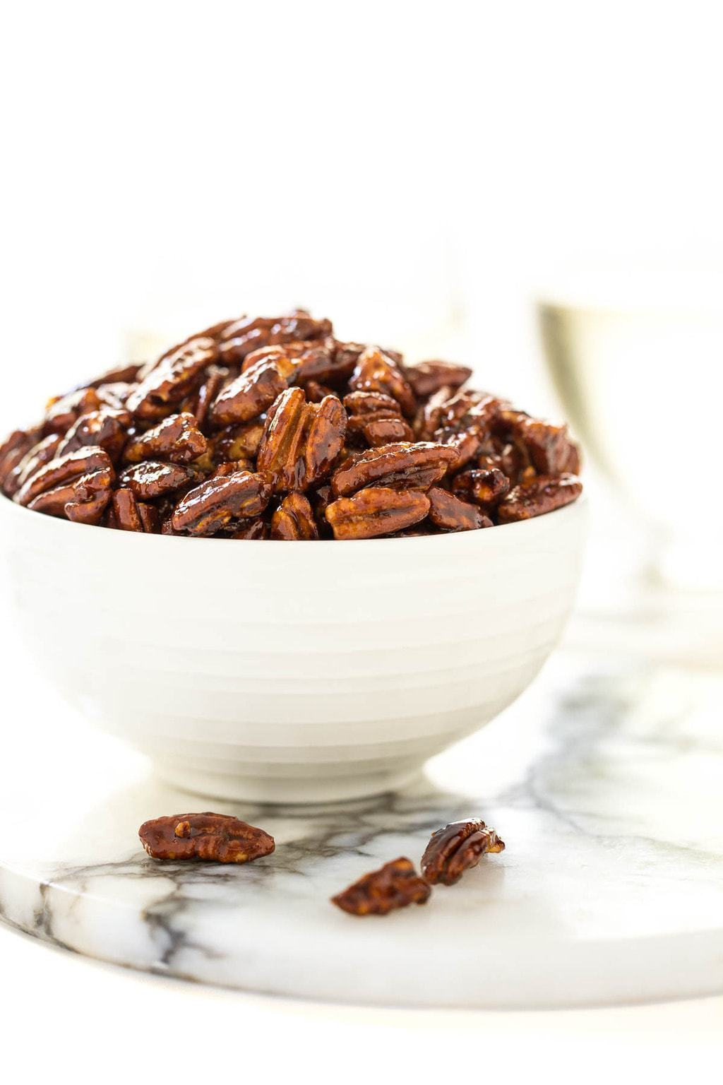 Vertical closeup photo of a cup of Easy Candied Pecans on a white marble surface.