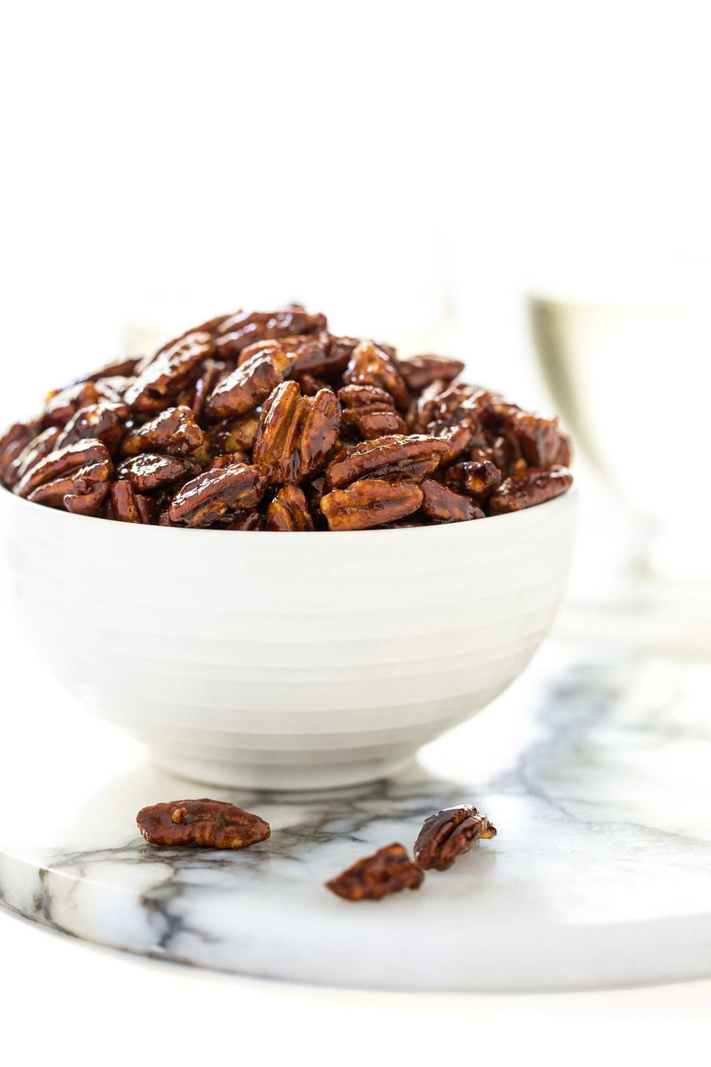 Medium photo of a white bowl of Easy Candied Pecans on a white and grey round marble slab.