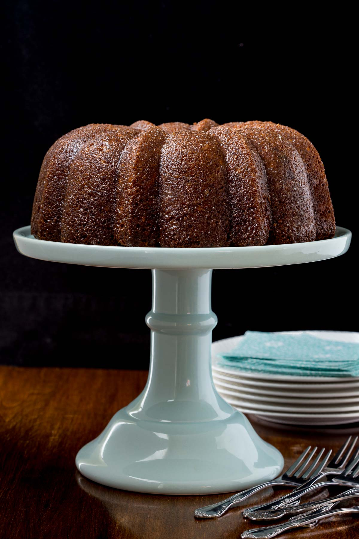 Photo of an Easy Carrot Cake with Buttermilk Glaze on a pale blue pedestal cake stand against a black background.