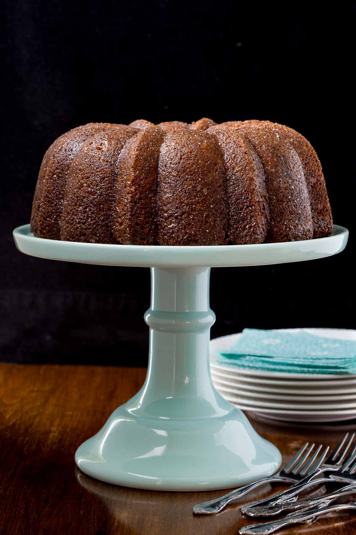 Photo of a Easy Carrot Cake with Buttermilk Glaze on a turquoise cake stand on a wood table.